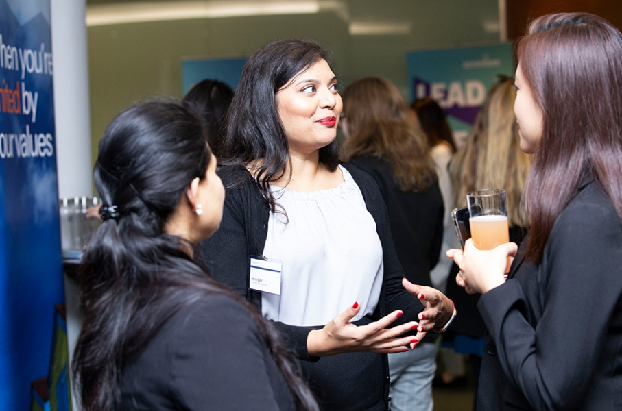 Group of three female-identifying individuals standing in conversation at a Cityview event