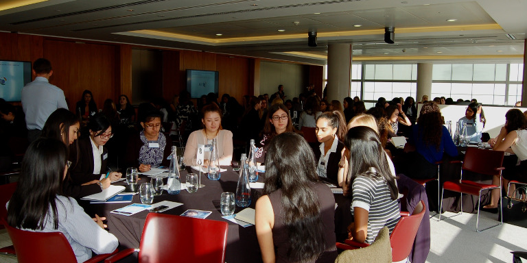 Room full of female-identifying students sitting around tables in groups at a Stand Out event
