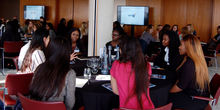 Group of diverse female-identifying students sitting and conversing at a Stand Out event