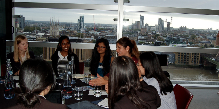 Group of female-identifying students sitting and conversing at a Stand Out event, with the London skyline behind them