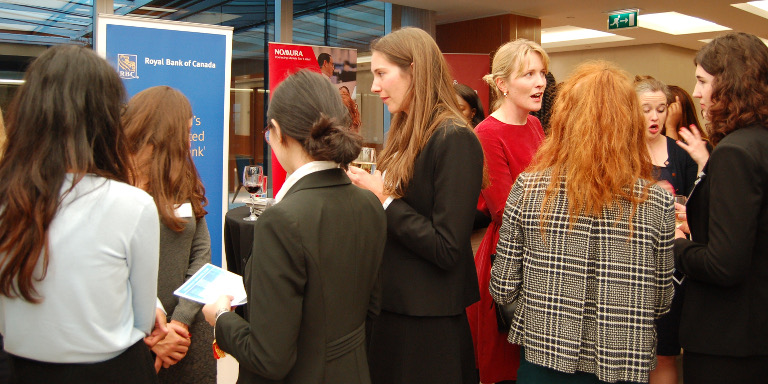 Groups of female-identifying students networking with industry professionals during a Stand Out event