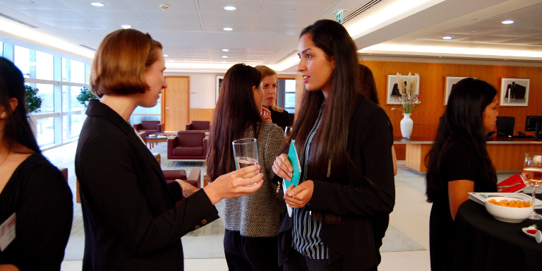 Female-identifying individuals networking over drinks during a Stand Out event