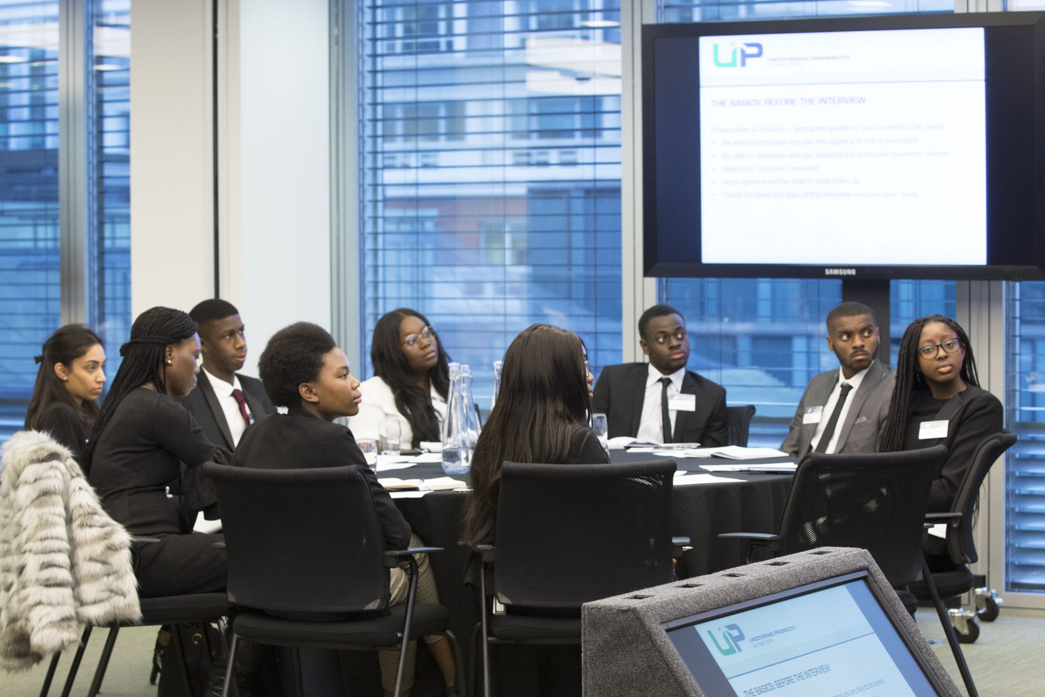 Group of diverse students sitting and watching a presentation during an Uncovering Prospects event