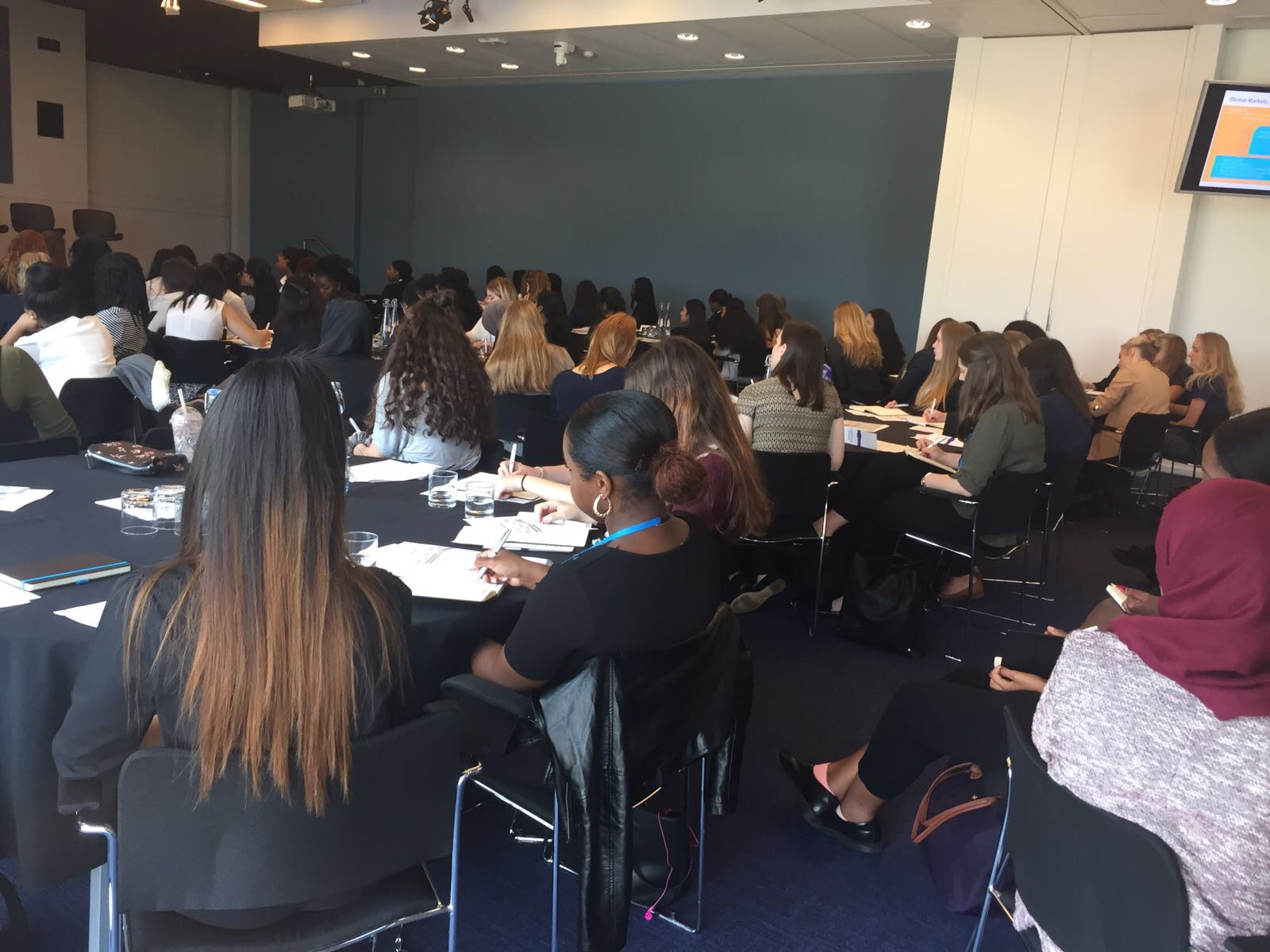 Room full of female-identifying students sitting and watching a presentation at an Open Doors event
