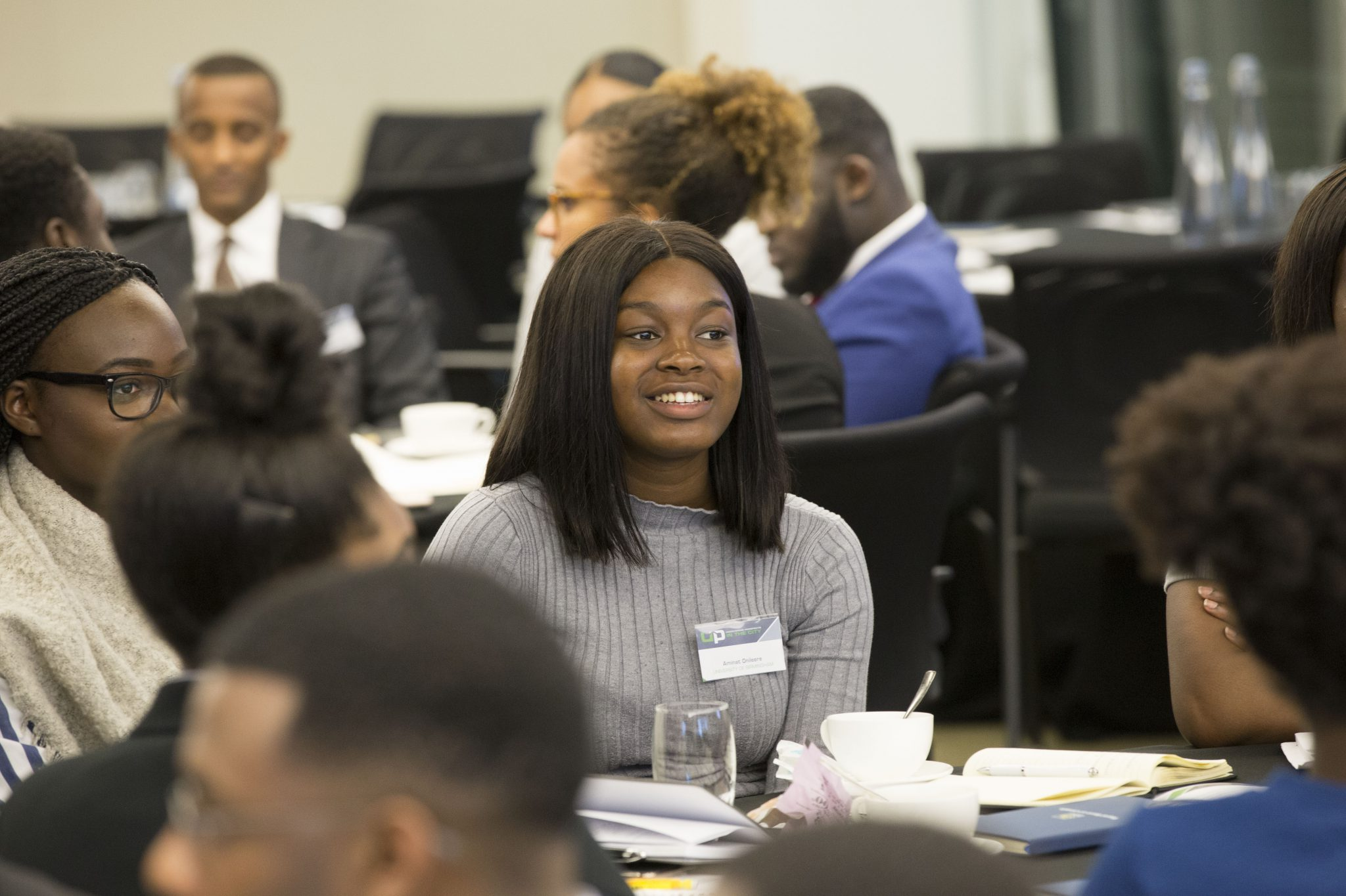 Diverse student sitting and smiling surrounded by their peers at an Uncovering Prospects event