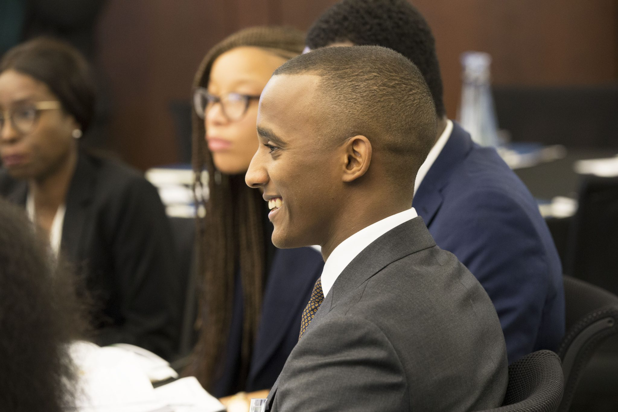 Diverse student sitting and smiling amongst their peers at an Uncovering Prospects event