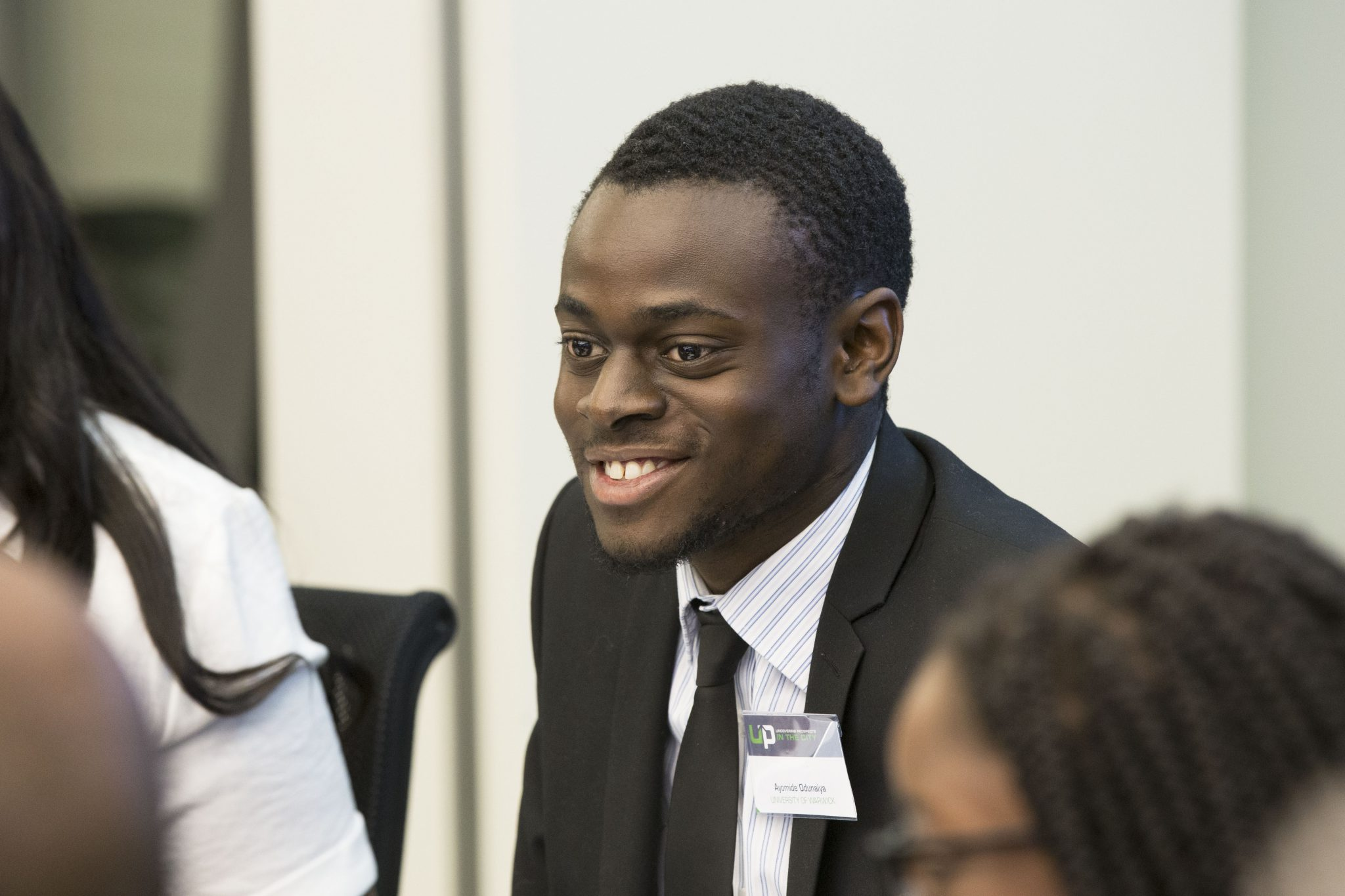 Diverse student sitting and smiling during an Uncovering Prospects event