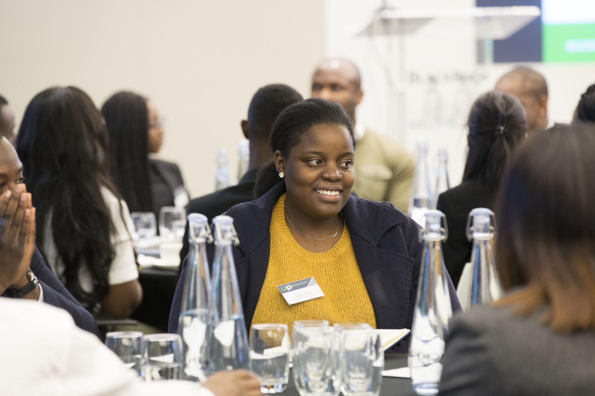 Diverse student sitting in a group of peers and smiling at an Uncovering Prospects event