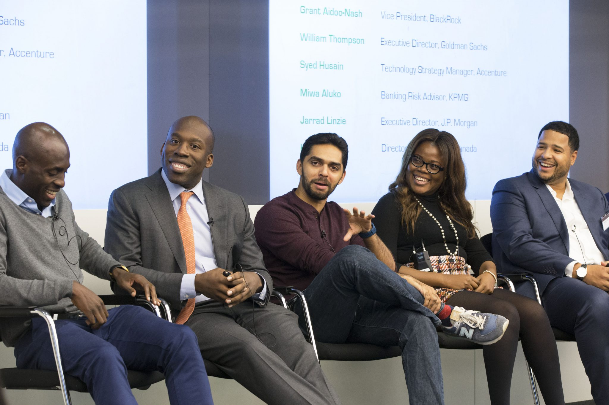 Diverse panel of five professionals sitting and smiling with a presentation behind them at an Uncovering Prospects event
