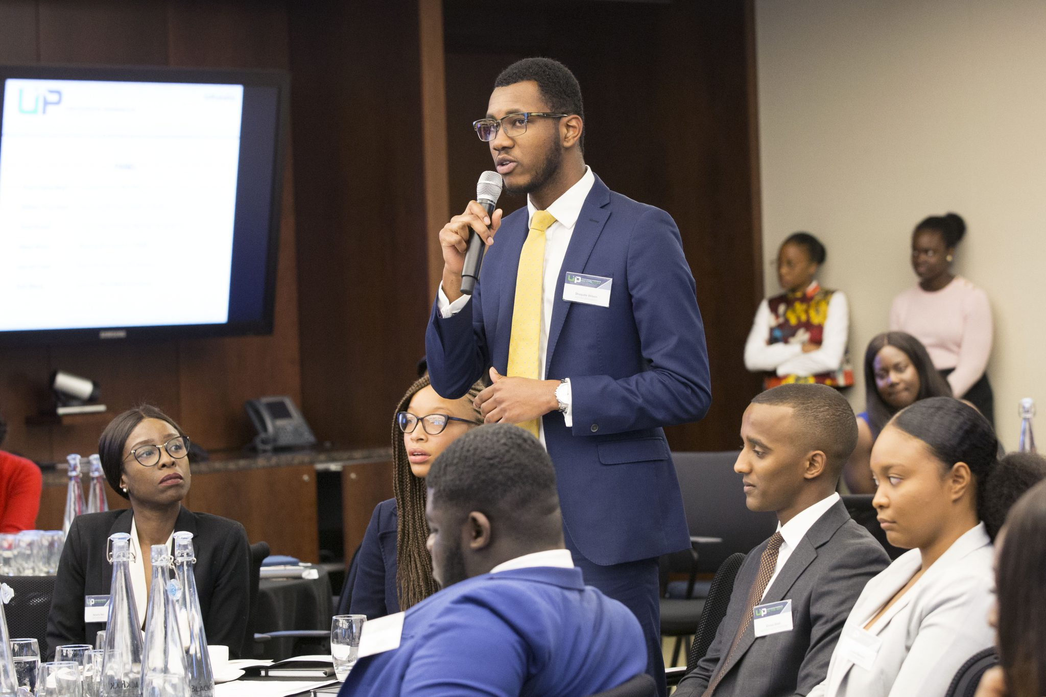 Diverse student standing and speaking into a microphone at an Uncovering Prospects event
