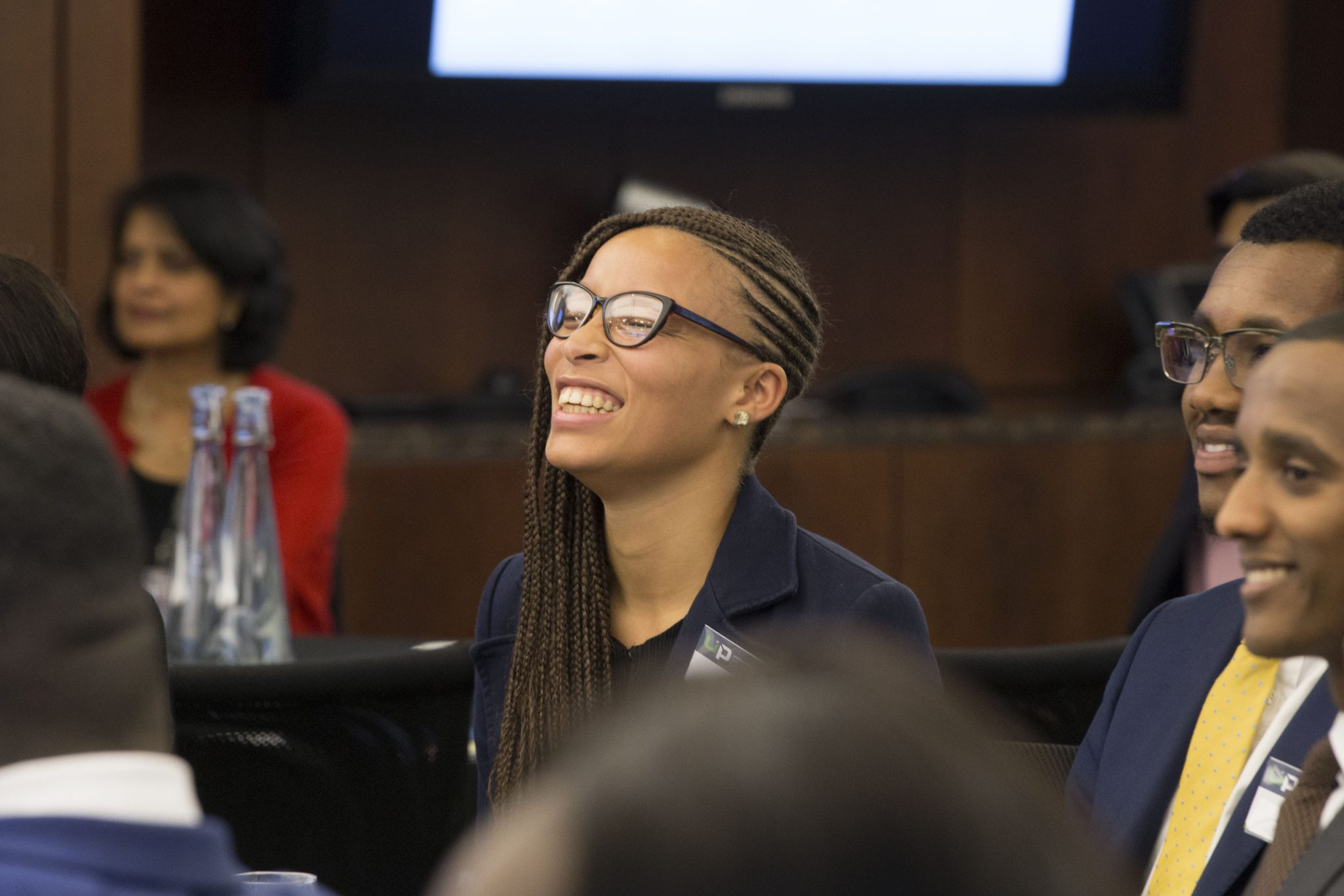 Diverse student sitting and smiling with their eyes shut during an Uncovering Prospects event