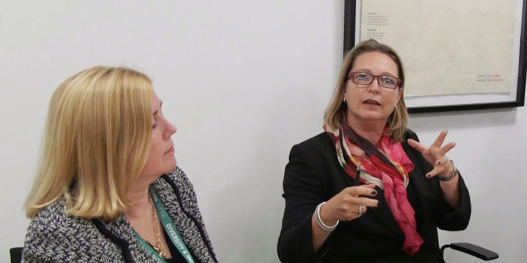 Two female-identifying professionals sitting and speaking to each other at a Stand Out event