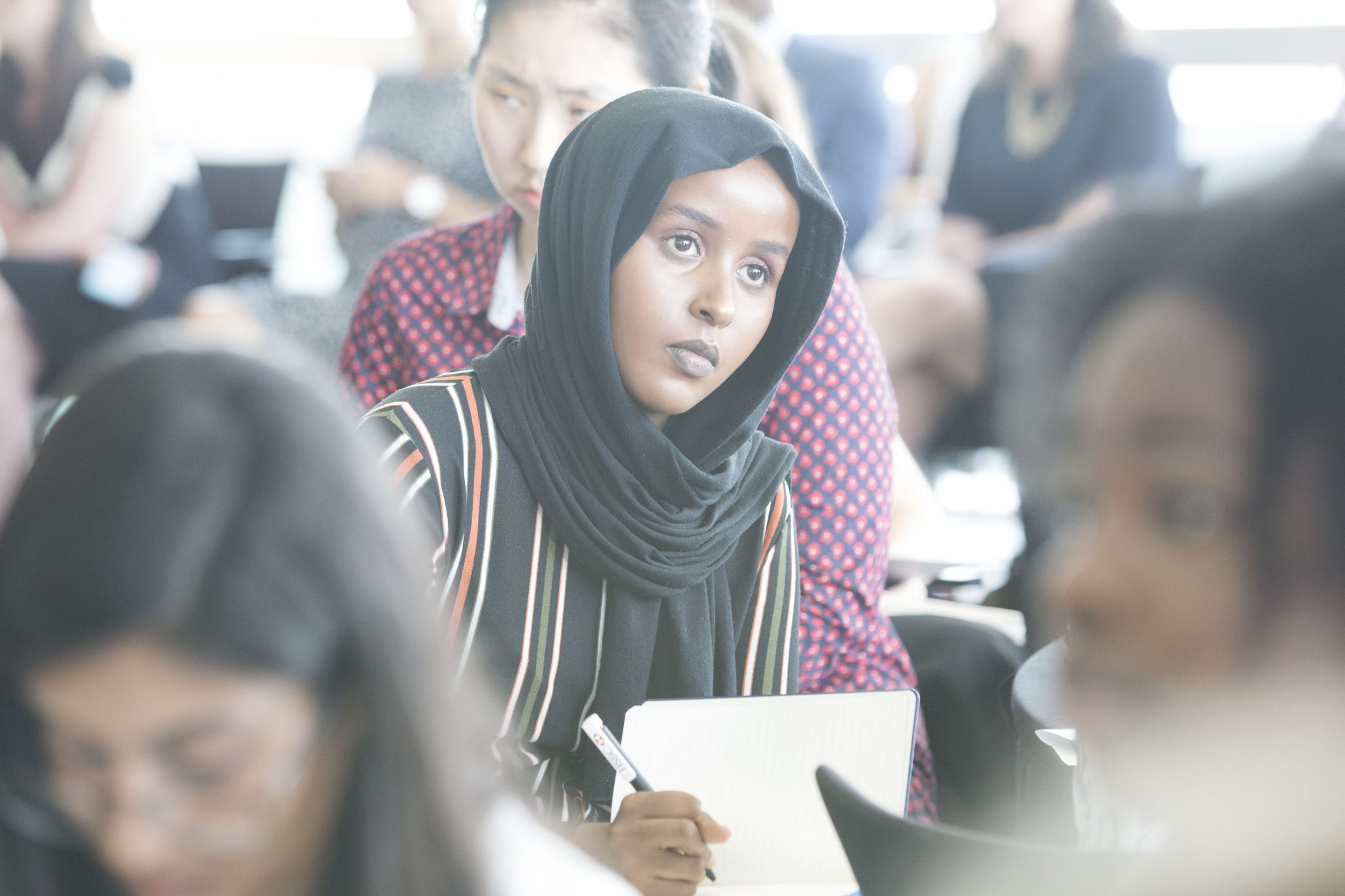 Female-identifying student wearing a hijab and writing in a notebook during a FreshLook event