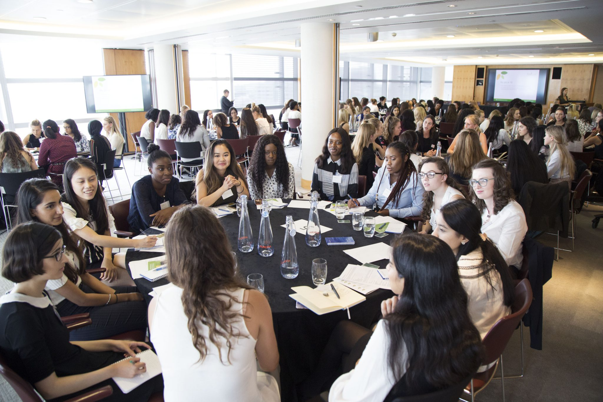 Group of female-identifying students sitting around a table in discussion at the FreshLook event