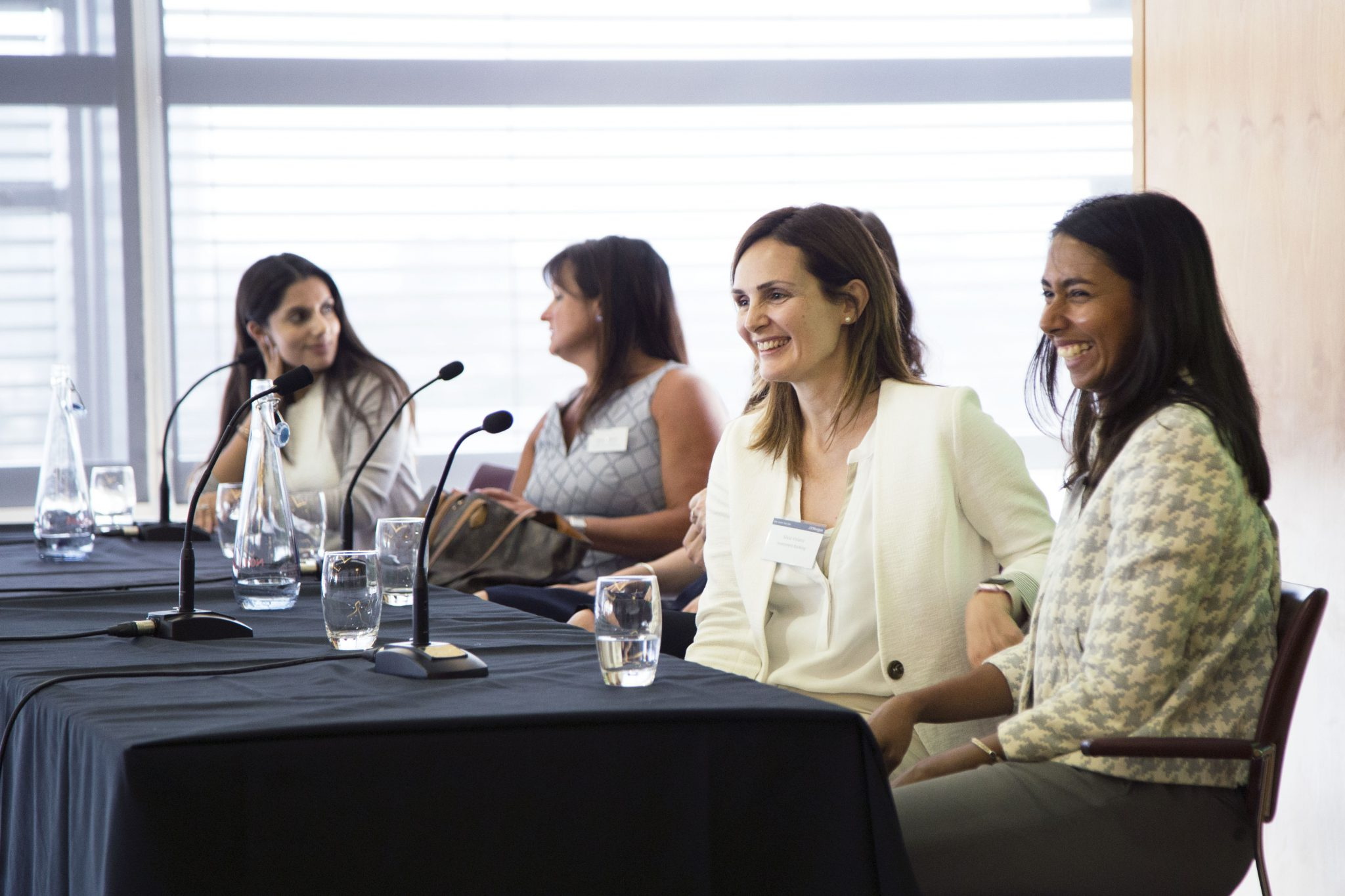 Panel of five female-identifying people sitting and smiling at a panel discussion desk during a FreshLook event