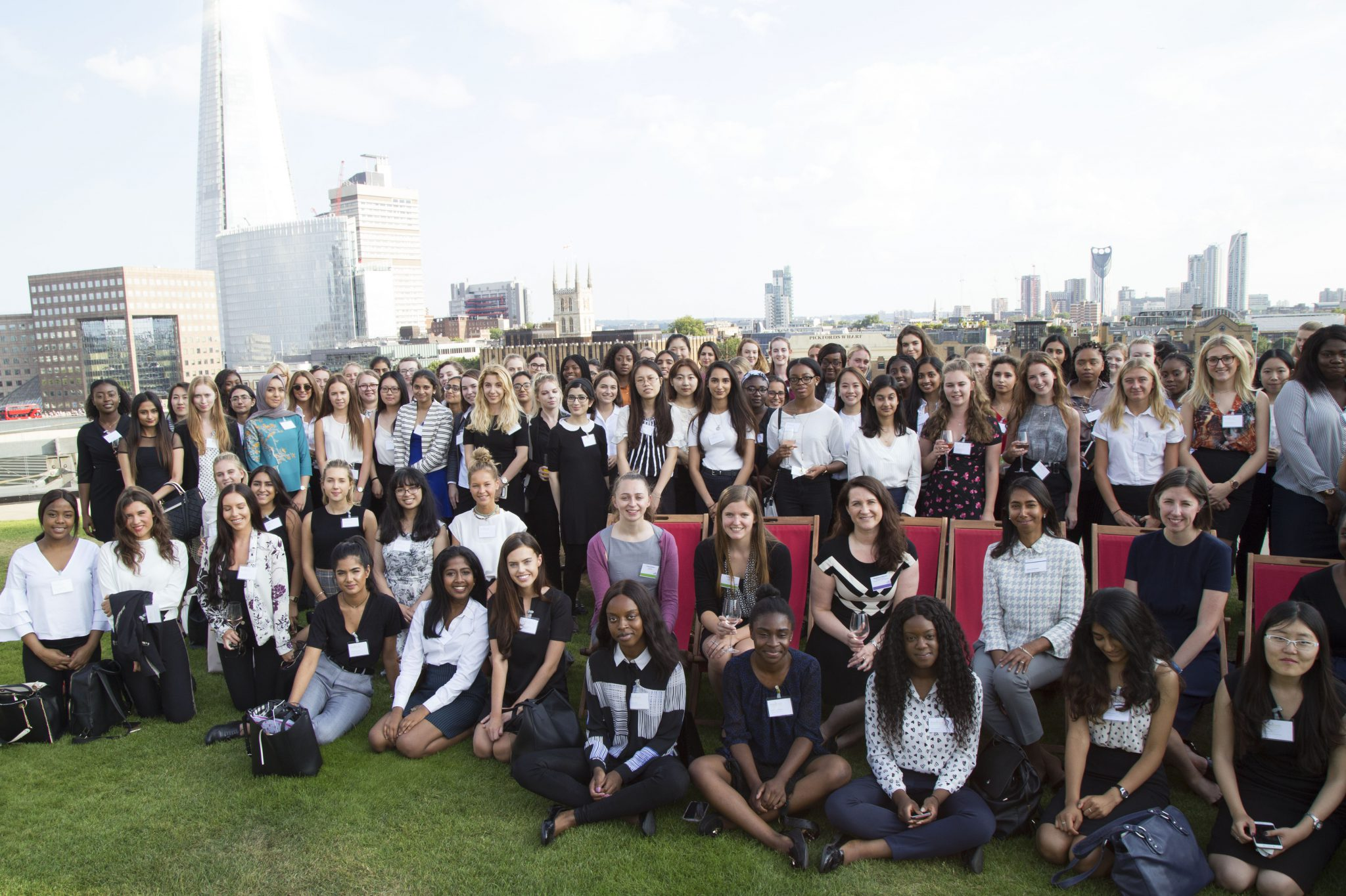 Large group of female-identifying students gathering outside with the London skyline behind them during a FreshLook event