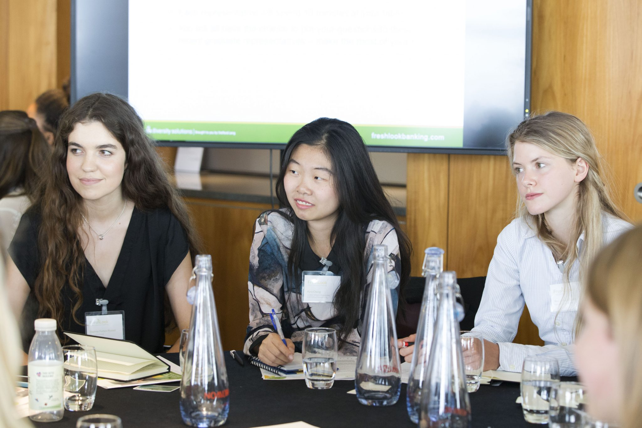 Three female-identifying students listening to their peers during a FreshLook event