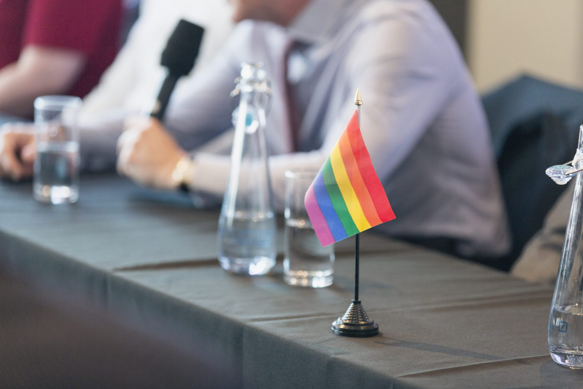 LGBTQ+ flag standing on a table at an Inside & Out event, with someone speaking into a microphone in the background