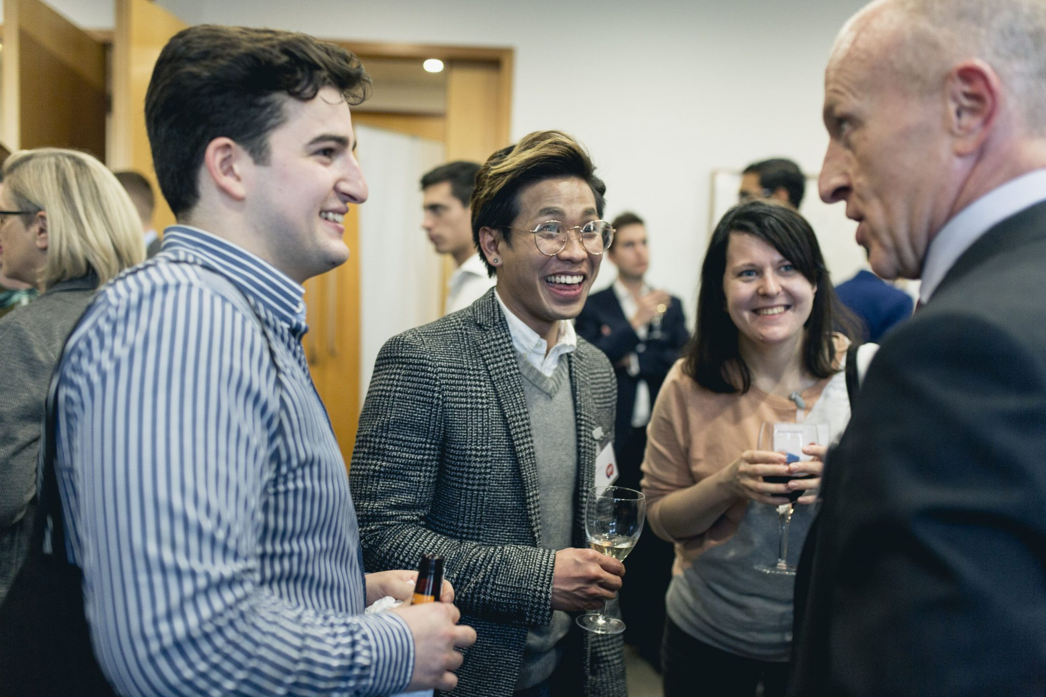 Students smiling and networking with industry experts at an Inside & Out LGBTQ+ event, with drinks in their hands